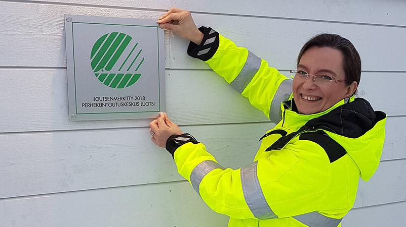 Heidi Karlsson laatupäällikkö kiinnittää Joutsenmerkkikylttiä
