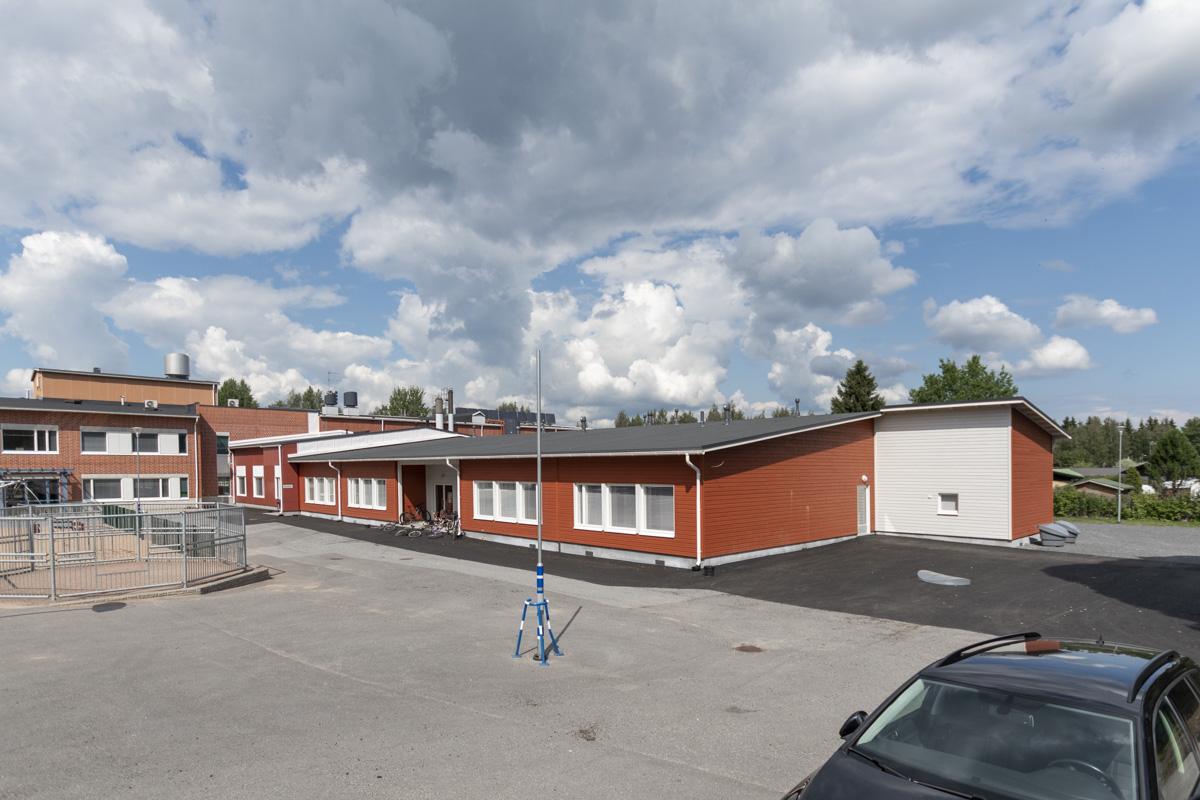 lisärakennus vanhaan koulurakennukseen yhdistettynä etupiha.